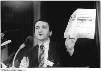 Wolfgang Schnur beim Gründungsparteitag des Demokratischen Aufbruchs am 16. Dezember 1989 in Leipzig, Von Bundesarchiv, Bild 183-1989-1216-021 / Gahlbeck, Friedrich / CC-BY-SA 3.0, CC BY-SA 3.0 de, https://commons.wikimedia.org/w/index.php?curid=5424937