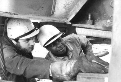 ADN-ZB Weisflog 12.7.84 Berzirk Cottbus: Großinstandsetzung- Konstantino Monjanl (r. ) gehört zu den 40 Mocambiquanern die im Braunkohlewerk Welzow eine Ausbildung als Meister erhalten. Er ist seit 5 Jahren in der DDR und spezialisiert sich auf die Instandsetzung von Tagebaugroßgeräten, nachdem er den Beruf eines Instandhalters erlernt hat. Links: Jens Wilhelm -siehe auch 1984-0712-9N-